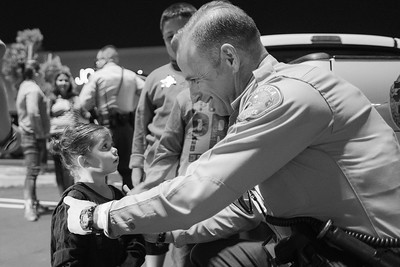 A deputy at the Promenade Mall comforts a child by giving her a deputy star sticker.
