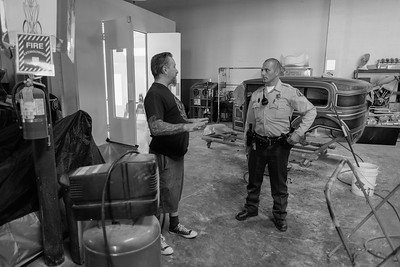 A deputy, having responded to a silent burger alarm, speaks with the owner of the shop. The shopkeeper operates a custom auto body painting and detailing shop.