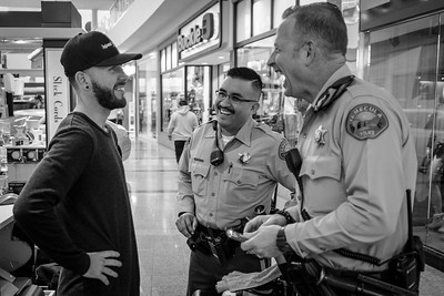 Two deputies from the Promenade Mall team share a lighthearted moment with a shopkeeper.