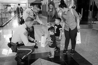 Two deputy's on patrol in the Promenade Mall, give badge stickers to two young shoppers.