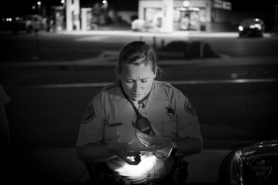 A deputy examines the registration of a vehicle pulled over for failing to stop at a red light. The driver was distracted while looking for a address on her mobile device.