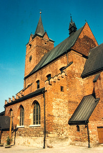 "PILZNO - The Catholic Church, seen from the southeast side.  A priest was once asked why Polish churches look so plain on the outside. His reply was, ""We didn't want any one to know that kinds of riches we had inside the church."" Polish churches generally have one rule, the plainer they look on the outside, the more ornate they are inside. This church is no exception."