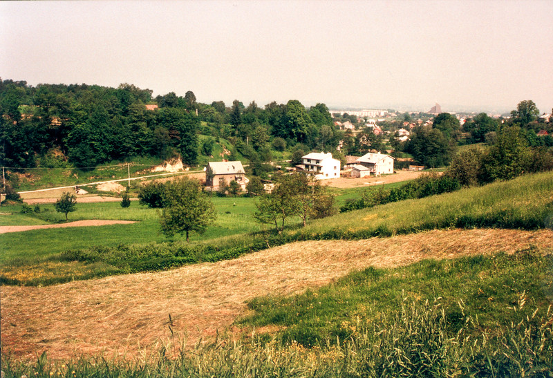 GAWRZYLOWA - The village straddles a shallow valley and sits on two opposing hillsides. This view looks from the eastern hill over the the western hill, with Debica seen in the distance. The large brick structure on the horizon is the new Catholic Church being built on the west side of Debica.
