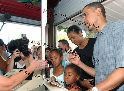 U.S. Senator, and Democratic presidential candidate Barack Obama, his wife Michelle Obama, their daughters Sasha Obama, right, and Malia Obama, order lunch at the Iowa Pork Producers stand during a visit to the Iowa State Fair, Thursday August 16, 2007 in Des Moines, Iowa.