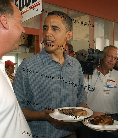 U.S. Senator, and Democratic presidential candidate Barack Obama carries some port chops back to their table as he and his family spent time at the Iowa State Fair, Thursday August 16, 2007 in Des Moines, Iowa.
