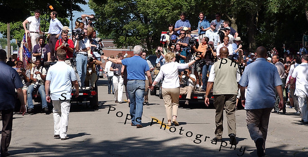 Senator and Democratic presidential hopeful Hillary Clinton, and her husband, former president Bill Clinton with a horde of media and security, march in the Independence Day Parade  in Clear Lake, Iowa, 4 July, 2007.