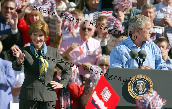 First lady Laura Bush greets supporters as President George W. Bush looks out at the crowd at the start of a rally in Waterloo, Iowa Saturday Oct. 10, 2004. The day after the second of three debates with Sen. John Kerry the Democratic opponent, Bush was back on the campaign trail. (EPA/Steve Pope)