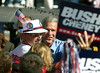 President George W. Bush mugs for a photo with a supporter after speaking at a rally in Waterloo, Iowa Saturday Oct. 10, 2004. The day after the second of three debates with Sen. John Kerry the Democratic opponent, Bush was back on the campaign trail. (EPA/Steve Pope)