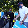 State Rep. Dave Nangle, D-Lowell, and Vanna Howard, one of two challengers in the Democratic primary for the 17th Middlesex district, stand with their respective supporters outside the Reilly Elementary School polling place. Vanna Howard meets a supporter, Gabriel Fonseca of Lowell, right, with his dog Luna, who's just chewed her leash through and was loose. Howard said Luna must smell her own dog, a Bichon. (SUN/Julia Malakie)