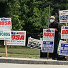 From left, Dave Marino, Bart Hogan, and his wife Jodi Hogan holds signs for theire candidates in the Billerica Town Election at Parker Elementary School. (SUN/Julia Malakie)