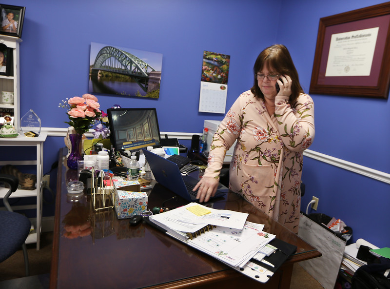 State Rep. Colleen Garry, at her law office in Dracut, checks on the status of he state legislature's expected first remote vote, learning that it was not going to happen today, due to objections.  (SUN/Julia Malakie)