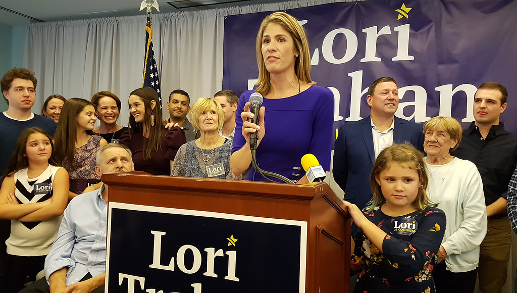 . Lori Trahan is surrounded by family members including niece Ellie D\'Amico, 8, of Andover, left, parents Tony and Linda Loureiro, at left, husband David Trahan, second from right rear, David\'s mother Lorraine Trahan of Tyngsboro, and daughter Grace, 8, after winning the 3rd Congressional District seat. (SUN/Julia Malakie)