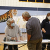 Littleton High School, the polling place this year. Voter Paul Biagioni checks in with poll volunteers Marilyn Converse, left, and Melissa Dunn. JULIA MALAKIE/LOWELLSUN