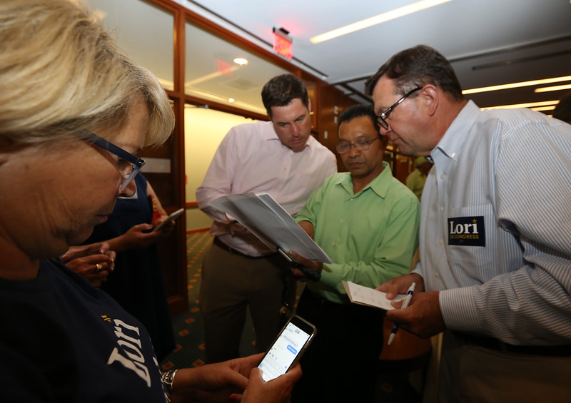 Lori Trahan primary night party for Massachusetts 3rd Congressional District Democratic primary. From left, supporters Tracy Pazzella of Newburyport (whose daughter was Trahan's finance director until she had to leave to start her first year at Georgetown), Trahan's cousin Mike Dubuque of Westford, Hap Roeun of Chelmsford, and Enterprise Bank VP Jim Moriarty, check early returns. (SUN/Julia Malakie)