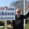 Candidate for Tewksbury Board of Selectmen Todd Johnson, who was previously a selectman and hopes to rejoin the board, holds a sign on Main Street in front of Town Hall.  JULIA MALAKIE/LOWELLSUN