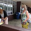 Signholders and voter check-in at the Middle School for Tyngsboro town election. Warden Colleen Gabriel checks in voter Caroline Lord. Gabriel was checking in people outdoors, and limiting the number who could be inside at a time. (SUN/Julia Malakie)