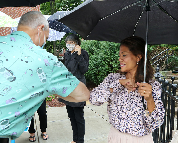 Vanna Howard, winner of the Democratic primary for the 17th Middlesex district, gets an elbow bump from supporter Jim Wilde of Lowell on Market Street. At rear is supporter Sally Coulter of Lowell.  (SUN/Julia Malakie)