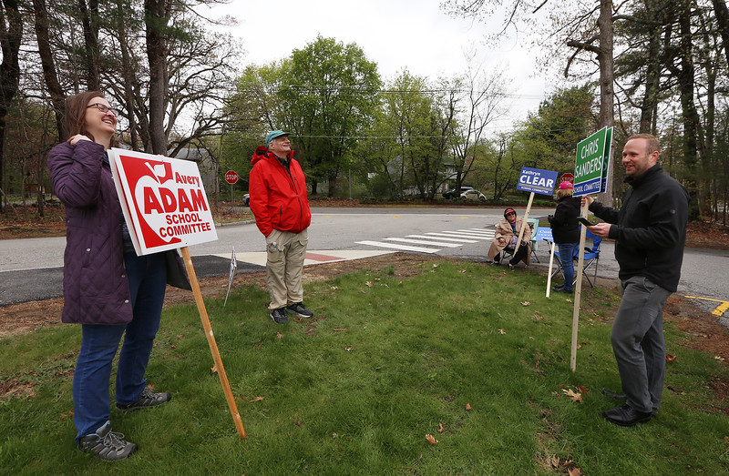 Westford town election, with contested races for Select Board and School Committee. From left front, Adam supporter Gloria Miller, Cunningham supporter Tom Spuhler, and School Committee candidate for reelection Chris Sanders, at the Robinson School. Spuhler's wife, seated at rear, was holding a sign for Kathryn Clear. JULIA MALAKIE/LOWELLSUN
