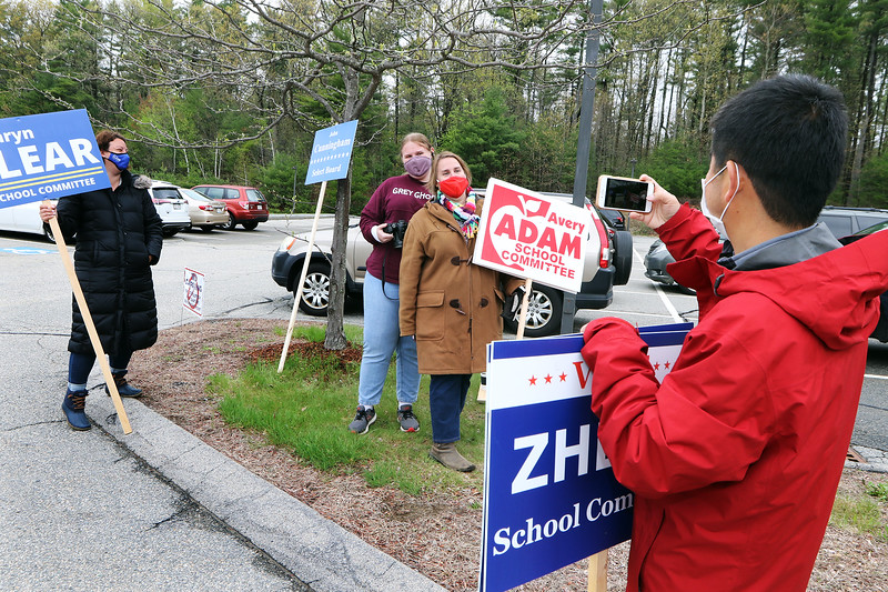 Westford town election, with contested races for Select Board and School Committee. School Committee candidate Mingquan Zheng takes a photo of fellow incumbent and candidate Avery Adam with her daughter, Westford Academy freshman Mackenzie Adam, 15, as challenger Kathryn Clear looks on, at the Miller School. JULIA MALAKIE/LOWELLSUN