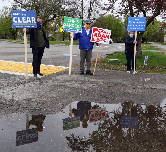 Westford town election, with contested races for Select Board and School Committee. From left, David Clear (Kathryn Clear's husband), Warren Adam (Avery Adam's husband), and Cunningham supporter Joyce Priestly, are reflected in a puddle as they hold signs at the Abbot School on a rainy election day.  JULIA MALAKIE/LOWELLSUN