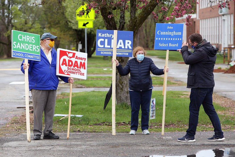 Westford town election, with contested races for Select Board and School Committee. From left, Warren Adam (Avery Adam's husband), Cunningham supporter Joyce Priestly, and David Clear (Kathryn's husband), arriving to take over holding his wife's sign at the Abbot School JULIA MALAKIE/LOWELLSUN