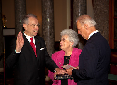 Vice President Joe Biden administers a ceremonial Senate oath during a mock swearing-in ceremony to Senator Chuck Grassley (R-IA), left, accompanied by his wife Barbara Ann, on Jan. 5, 2011, in the Old Senate Chamber on Capitol Hill in Washington DC. (Photo by Jeff Malet)