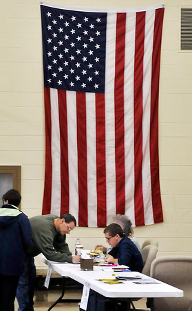 John P. Cleary |  The Herald Bulletin<br /> This voter signs the polling book in Union 3 under the large American flag on the wall at Mill Creek Civic Center in Chesterfield.