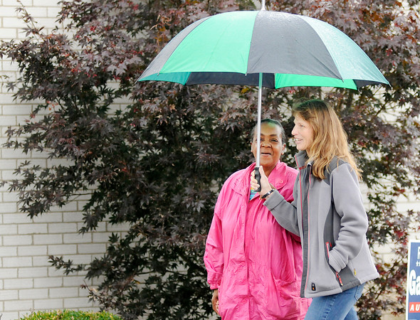 Don Knight | The Herald Bulletin<br /> Christine Dudley, wife of incumbent judge Mark Dudley shares her umbrella with Loretta Wilson as a light rain fell at the Anderson Zion Baptist Church on Tuesday afternoon.