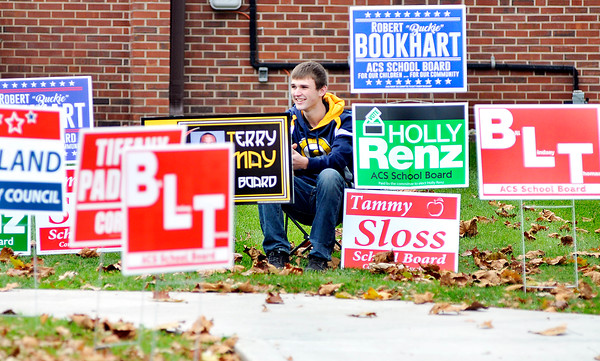 John P. Cleary |  The Herald Bulletin<br /> One of the few volunteers out working the polls was Brian Bevel, 17, here halfway obscured by all the campaign signs in front of Ward 1, Precinct 6 at East Side Church of God.