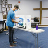 Jordan Armogun cleans a voting machine at Glad Tidings in Anderson. Cleaning machines and cotton swabs for activating touch screens were some of the COVID-19 precautions taken during the primary.