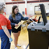 Jenna Lee helps Karen Myers scan her ballot at Highland Middle School on Tuesday.