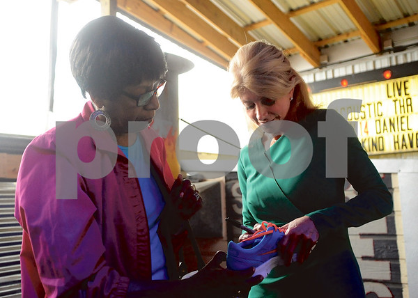Davis signs a brightly-colored running shoe for Lula Hinton, of Jacksonville, an ode to Davis' 11-hour-long filibuster to block Texas Senate Bill 5 in June. (Victor Texcucano/Staff)