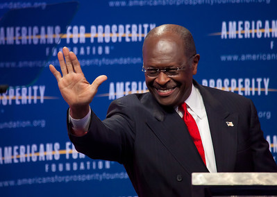 Herman Cain waves in the direction of David Koch at the conclusion of his speech