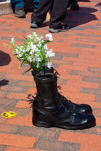 Jude Morford of womenstanding In August of 2006, with the ongoing intensity of the wars and with it the profound loss of human life, womenstanding began it's journey. With my granddaughter, Gabrielle standing next to me, we began the visual of peace by holding white flowers in our hands.   Each Sunday afternoon for one hour, together we stood on the North 45th exit overpass in Seattle, quietly in respect, to honor the lives killed and for the intention of peace.  In late January of 2007, the used black combat boots were added to our stand. Placing the flowers in one boot, to be a constant reminder to all who viewed those boots with flowers, of the lives no longer here..  In gratitude and with a deep understanding of this mission, there are those who have been touched by the essence of this movement and have begun the journey, carrying of boots with flowers.  We are to date a small group of individuals, standing alone on corners, overpasses, in front of Federal Bldgs, entrances to military bases, dedicating ourselves to presenting what we need most on this earth, peace...