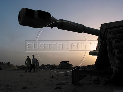 Scavengers walk past a tank cannon at dawn as they start their day of looking for useful materials from an old tank at a junk yard of scrap military hardware, an eerie desert momument to Iraq's history of wars with Iran, Kuwait and the United States, south of Baghdad.(Australfoto/Douglas Engle)