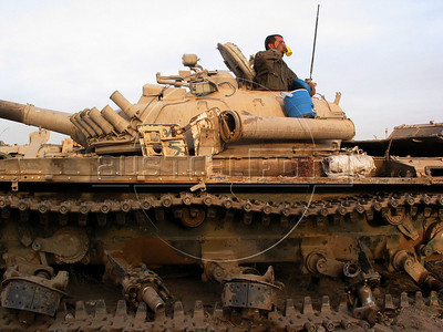 A scavenger takes a break from removing useful materials from an old tank at a junk yard of scrap military hardware, an eerie desert momument to Iraq's history of wars with Iran, Kuwait and the United States, south of Baghdad.(Australfoto/Douglas Engle)