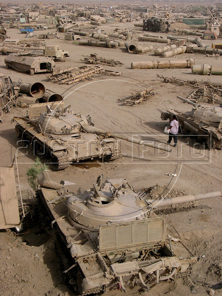 A scavenger walks past old tanks at a junk yard of scrap military hardware, an eerie desert momument to Iraq's history of wars with Iran, Kuwait and the United States, south of Baghdad.(Australfoto/Douglas Engle)
