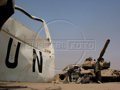Scavengers remove materials from an old tank beside a destroyed United Nations car at a junk yard of scrap military hardware, an eerie desert momument to Iraq's history of wars with Iran, Kuwait and the United States, south of Baghdad.(Australfoto/Douglas Engle)