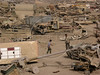 Boys walk on a scrapped cannon at a junk yard of military hardware, an eerie desert momument to Iraq's history of wars with Iran, Kuwait and the United States, south of Baghdad.(Australfoto/Douglas Engle)