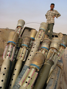 A scavenger stands near live ammunition at a junk yard of scrap military hardware, an eerie desert momument to Iraq's history of wars with Iran, Kuwait and the United States, south of Baghdad.(Australfoto/Douglas Engle)