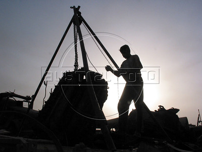 A scavenger removes the engine of a tank at a junk yard of scrap military hardware, an eerie desert momument to Iraq's history of wars with Iran, Kuwait and the United States, south of Baghdad.(Australfoto/Douglas Engle)