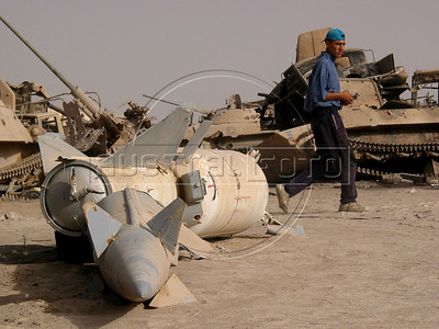 A scavenger walks past an old missile at a junk yard of scrap military hardware, an eerie desert momument to Iraq's history of wars with Iran, Kuwait and the United States, south of Baghdad.(Australfoto/Douglas Engle)