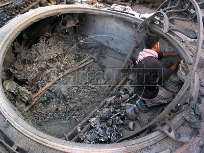 A scavenger removes materials from an old tank at a junk yard of scrap military hardware, an eerie desert momument to Iraq's history of wars with Iran, Kuwait and the United States, south of Baghdad.(Australfoto/Douglas Engle)