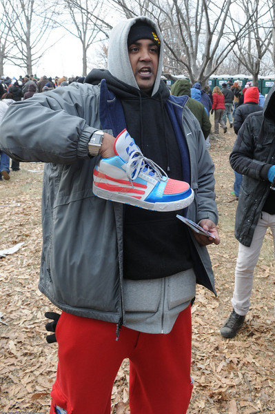 """(1 of 2) This guy was holding a protoype of his """"Barack's"""" sneaker and encouraging everyone to order online. (miblox)"""