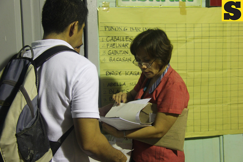 A board of election teller checks the election returns submitted for canvassing in Barangay Guadalupe Elementary School