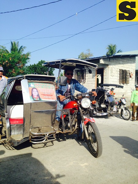 The tricycle still has a tarpaulin of a candidate