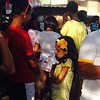 A kid squeezes in the crowd, holding flyers for candidates and distributing them outside Balagtas Elementary School in Bulacan