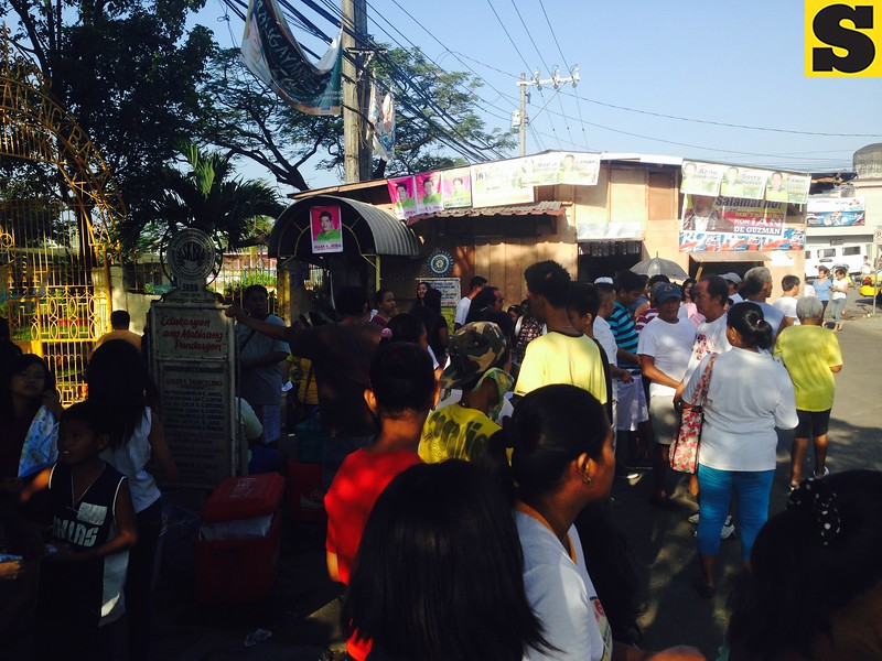 Voters, supporters of candidates gather outside Balagtas Elementary School in Bulacan (at around 8:00 am)