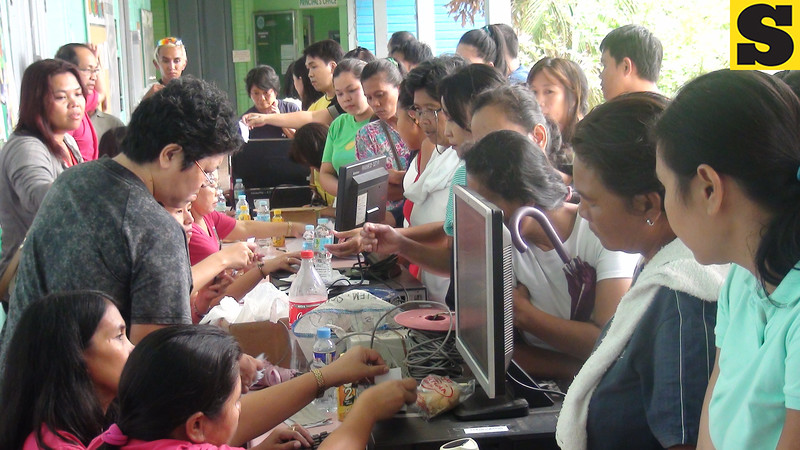 """CEBU. Comelec personnel and volunteers assist residents in Guadalupe who came to vote """"yes"""" or """"no"""" on Republic Act 9905, creating Banawa-Englis a separate barangay. (Laureen Mondonedo/Sunnex)"""