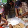 CEBU. Guadalupe residents looking at their precinct numbers from the folders readied at the tent of those voting yes to splitting Barangay Guadalupe into two. (Laureen Mondonedo/Sunnex)